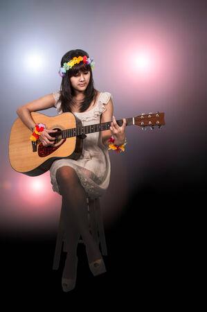 Beautiful young woman playing an acoustic guitar