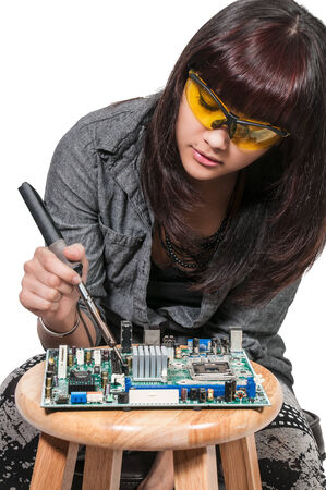 soldering: Beautiful woman repair soldering a printed circuit board Stock Photo