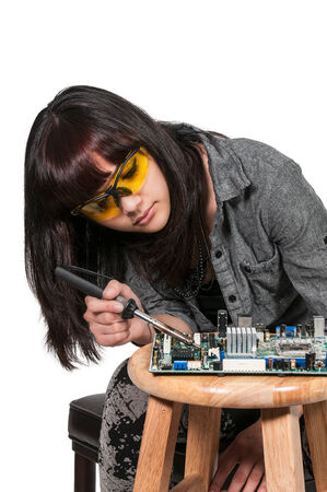 Beautiful woman repair soldering a printed circuit board photo