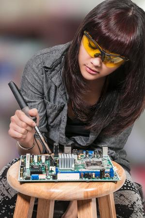 Beautiful woman repair soldering a printed circuit board Foto de archivo