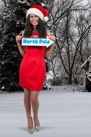 north pole: Beautiful woman with a Santa hat Christmas and a north pole sign Stock Photo