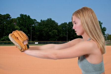 Beautiful woman catchinging a baseball at a ball field Stock Photo - 25885505