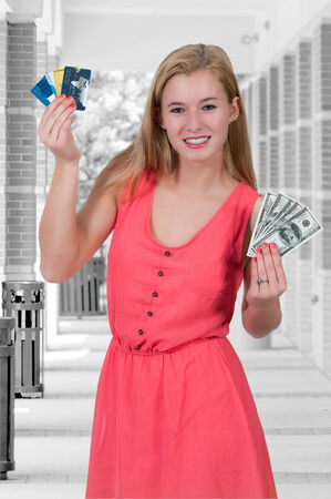 Beautiful woman holding a hand full of 100 dollar bills and credit cards 免版税图像