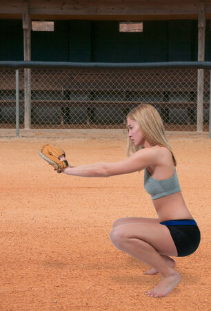 Beautiful woman catchinging a baseball at a ball field Stock Photo - 27218445