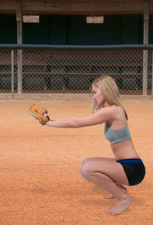 Beautiful woman catchinging a baseball at a ball field Stock Photo - 27218445