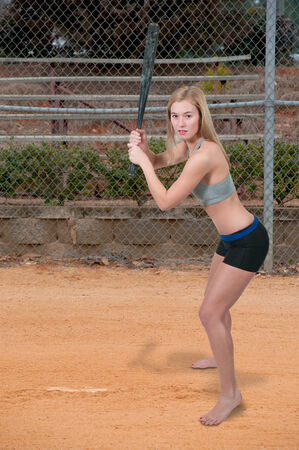Beautiful woman hitting a baseball with a bat photo