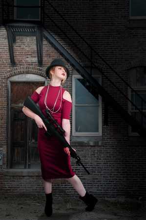 Beautiful young woman holding an automatic assault rifle