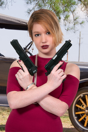 Beautiful young woman criminal with a gun photo