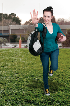 bookbag:  beautiful young woman student playing a game of football running with the ball