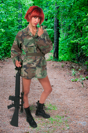 come hither: Beautiful young woman soldier with a pistol and rifle Stock Photo