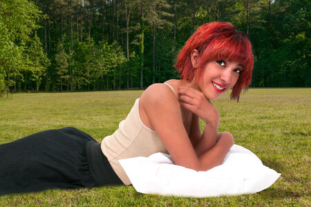 Beautiful young attractive woman laying down with a pillow