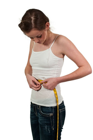 Beautiful woman measuring her waist with a tailors tape photo