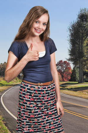 Teenage woman gesturing with a thumbs up photo