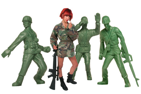 Beautiful young woman soldier with a pistol and rifle with toy soldiers photo