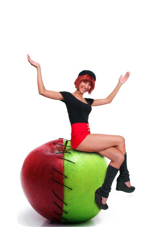 Beautiful woman sitting on a green and red sweet and sour apple photo