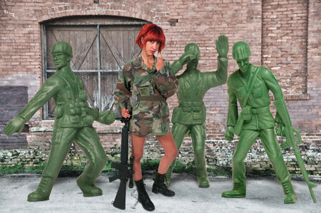 come hither: Beautiful young woman soldier with a pistol and rifle with toy soldiers