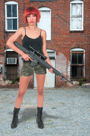 Beautiful young woman soldier with a M16 rifle photo