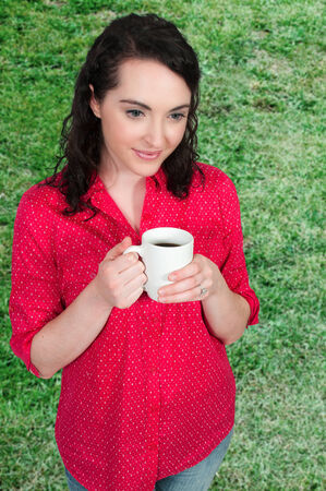 Beautiful young woman drinking coffee in the morning