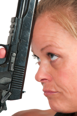 holding gun to head: Woman holding a gun to her head threatening suicide Stock Photo