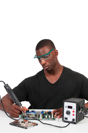 Man repairing a printed circuit board with a forced air soldering iron photo