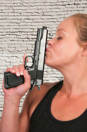 Beautiful woman in love with and kissing her gun photo