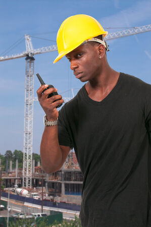 Handsome black man construction worker talking on a walkie talkie Banco de Imagens