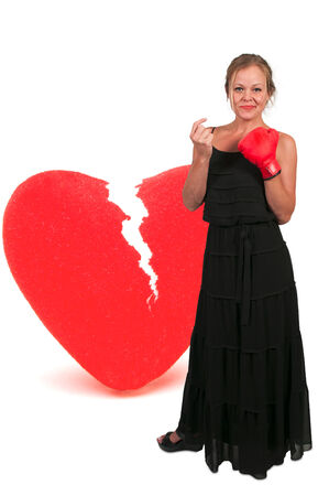 heartbreaker: Beautiful woman in wearing a boxing glove in front of a broken heart - heartbreaker Stock Photo