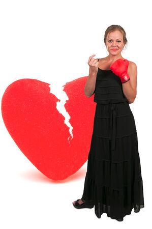 Beautiful woman in wearing a boxing glove in front of a broken heart - heartbreaker photo