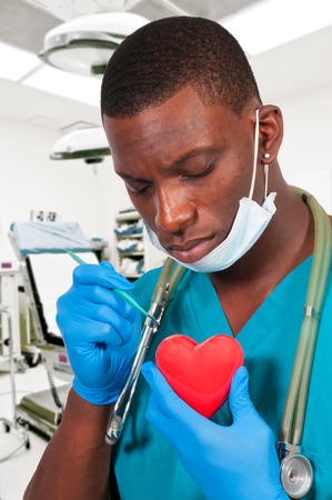 Handsome doctor cardiologist holding a red heart