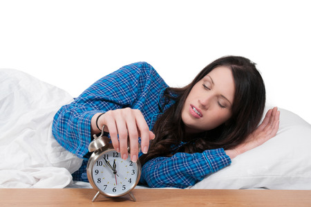 awakened: Beautiful young sleeping woman waking up with an alarm clock
