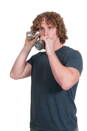 tin can phone: Young man using tin can phone technology Stock Photo