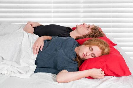 insomniac: Insomniac man laying next to sleeping wife Stock Photo