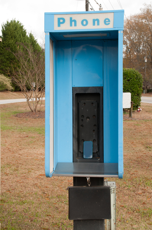 cell phone booth: Old phone booth with a cell phone