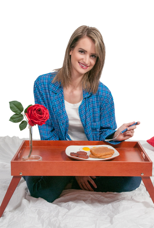 Beautiful woman eating a big breakfast in bed photo