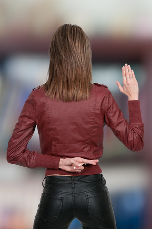 mislead: Beautiful woman with her fingers crossed behind her back Stock Photo