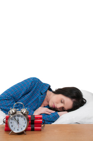 human time bomb: Beautiful young woman sleeping in bed with a time bomb alarm clock
