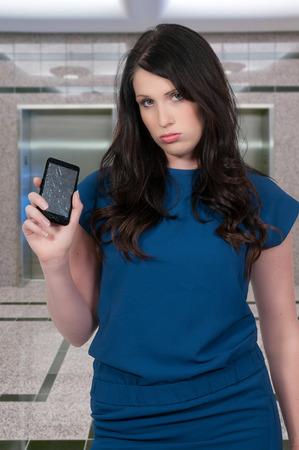 celulas humanas: Mujer hermosa con una pantalla de tel�fono agrietado roto Foto de archivo