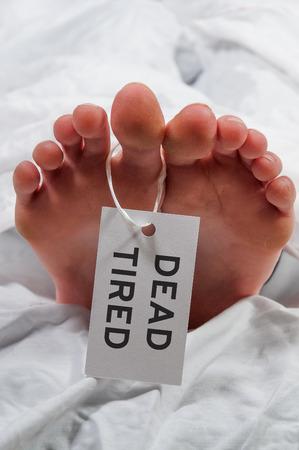 Practical joke toe tag on a tired asleep woman