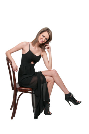 stilletto: Beautiful young woman in a dress and heels sitting Stock Photo