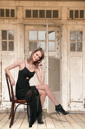 stilleto: Beautiful young woman in a dress and heels sitting Stock Photo