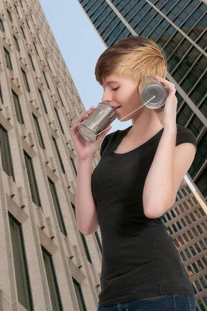 tin can phone: Woman talikng on a primative tin can phone