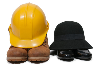 work boots: Steel toe work boots yellow hard hat cloche hat and black high heel shoes Stock Photo