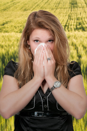 hanky: Beautiful woman with a cold, hay fever or allergies blowing her nose