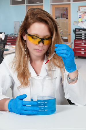eyedropper: Beautiful woman scientist investigating a glass beaker