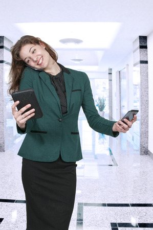 Beautiful woman talking texting and multitasking while juggling multiple cell phones and conversations Stock Photo - 39790295