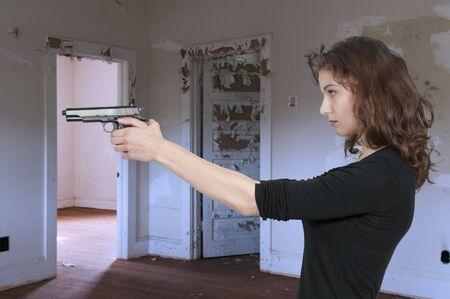 female assassin: Beautiful woman with a loaded handgun pistol