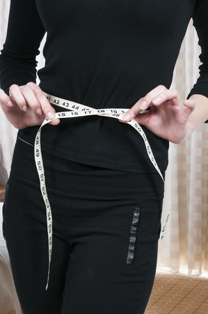 tailors tape: Beautiful woman measuring her waist with a tailors tape