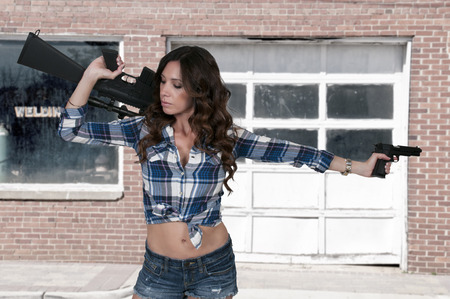 M16: Beautiful young woman soldier with a pistol and rifle Stock Photo
