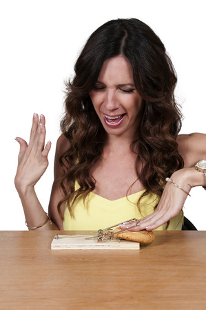 overindulgence: Beautiful woman using the mouse trap diet plan Stock Photo