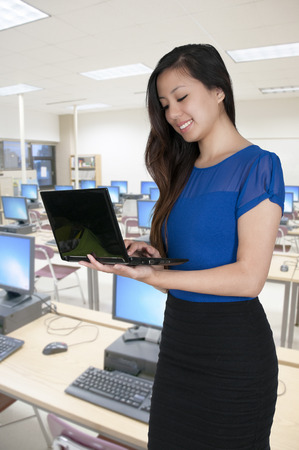 savvy: Beautiful computer savvy young woman using a laptop